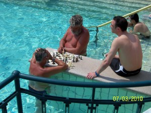 Very sunburned men playing chess in water.