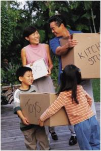 Smiling family carrying moving boxes