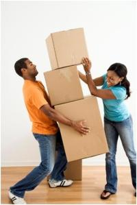 Smiling couple stacking moving boxes