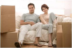 Couple sitting surrounded by moving boxes