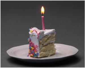 Picture of a piece of birthday cake with a lit candle